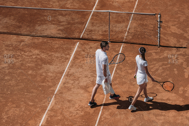 High angle view of young couple with rackets walking by tennis court