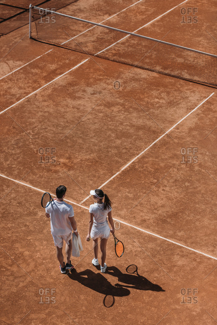 High angle view of sportive couple with rackets walking by tennis court