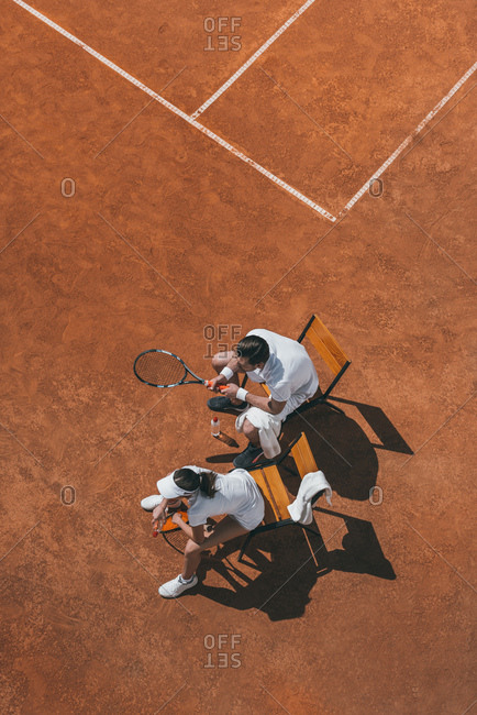 High angle view of young couple relaxing on chairs after tennis match