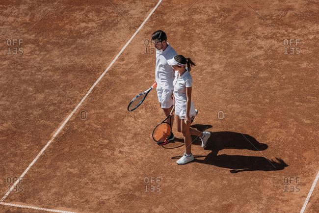 High angle view of young sportive couple with rackets walking by tennis court