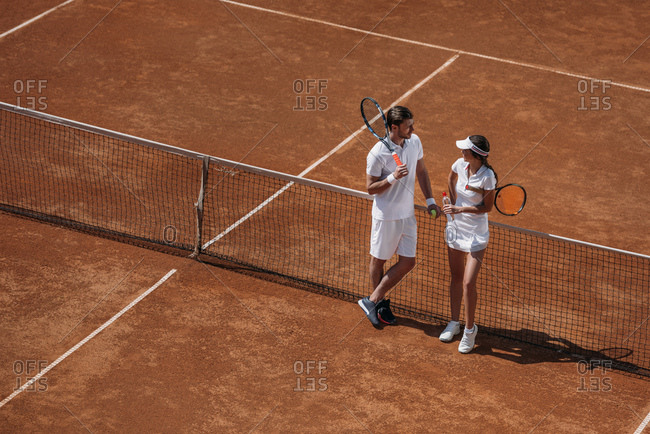 High angle view of young handsome man flirting with woman on tennis court