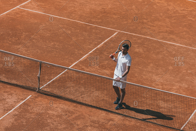 High angle view of man resting on tennis court after match