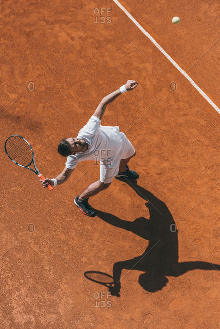High angle view of man making hit with tennis racket