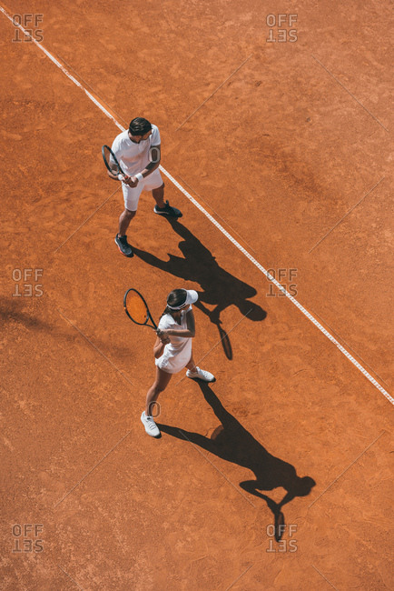 High angle view of young couple playing tennis as team