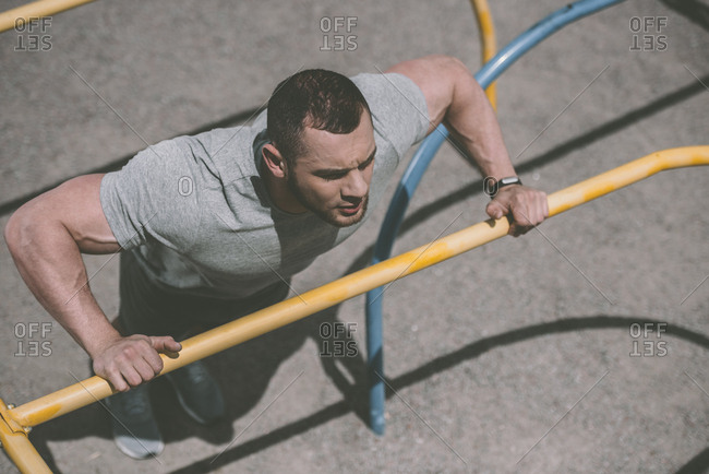 Overhead view of handsome sportsman doing push up at horizontal bar