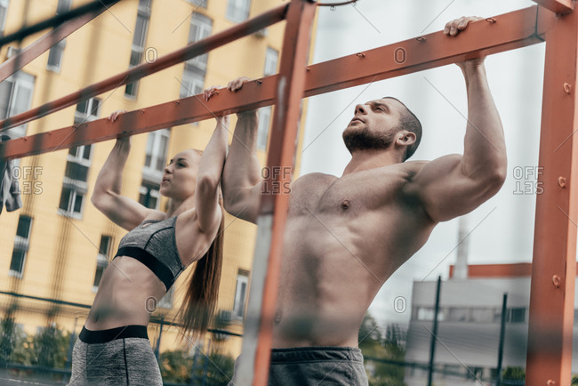 Sportsman and sportswoman pulling up at horizontal bar together