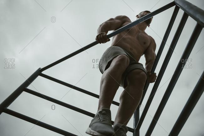Bottom view of sportsman pulling up at horizontal bar
