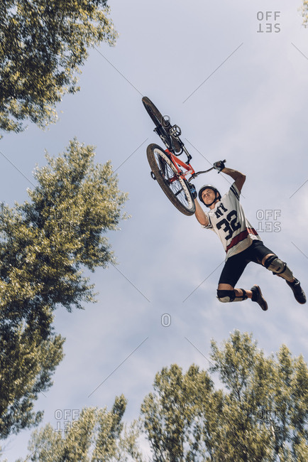Bottom view of sportsman jumping with bike