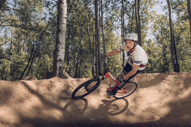 Cyclist riding mountain bike on track in forest
