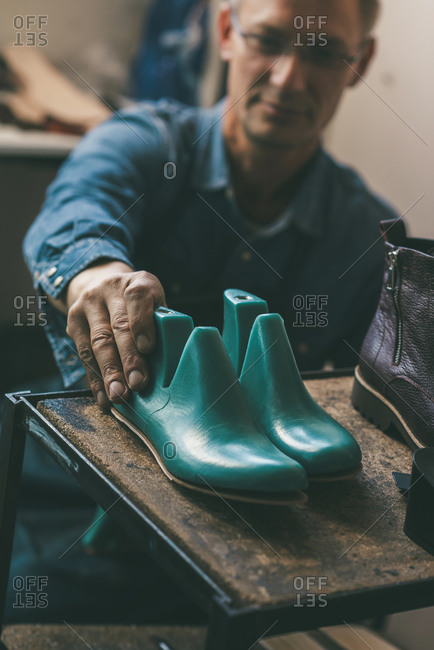 Selective focus of shoemaker holding footwear work pieces from shelf in workshop