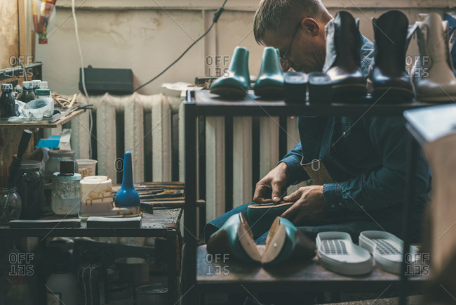 Experienced shoemaker creating shoes in workshop