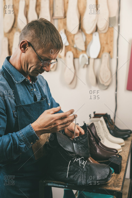 Mature shoemaker putting shoelaces into unfinished boots at workshop