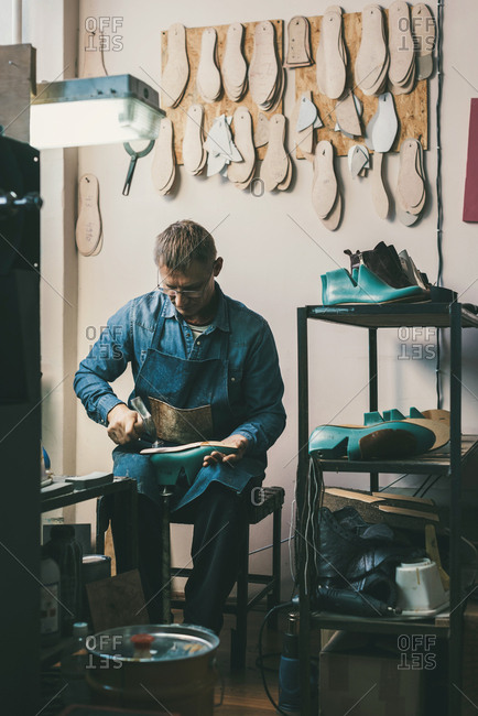 Mature shoemaker working with footwear work pieces at workshop