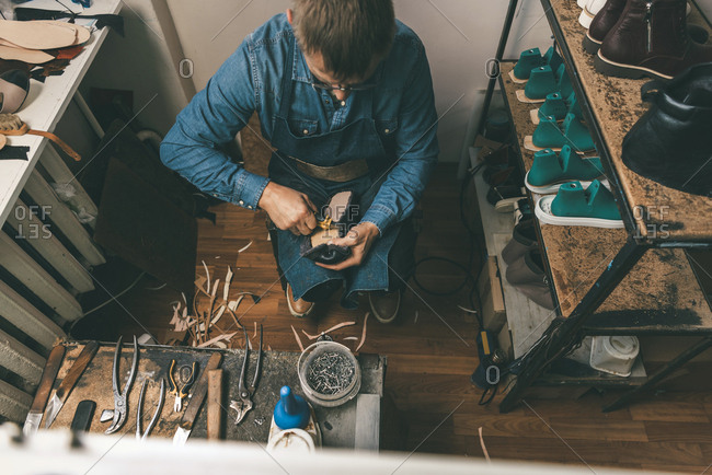 Overhead view of mature shoemaker working with diy tools in workshop