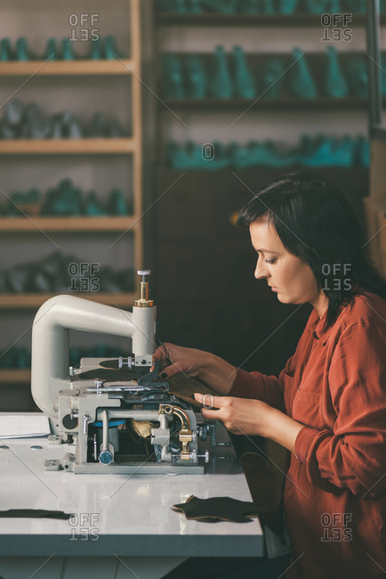 Side view of middle aged seamstress working with sewing machine and leather at shoemaker workshop