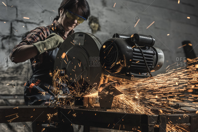Female welder in protective goggles using welding torch in workshop