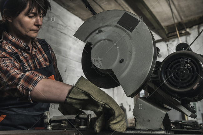 Concentrated female welder using welding torch in workshop