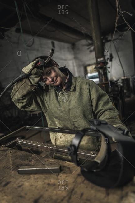 Tired female welder holding welding torch in workshop