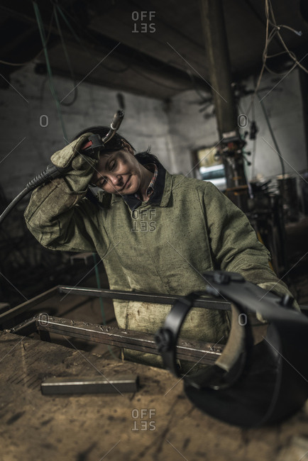 Tired female welder holding welding torch in workshop