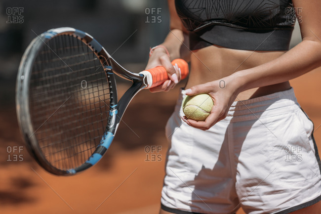 Cropped shot of athletic young woman with tennis racket and ball