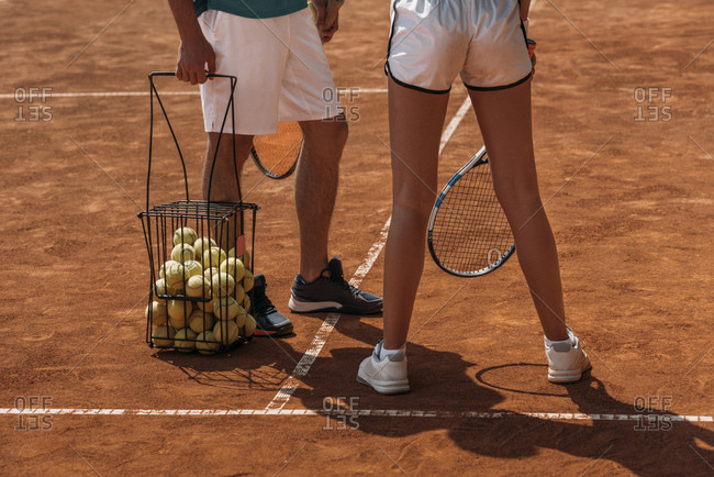 Cropped shot of couple in sportswear ready to play tennis on outdoor court
