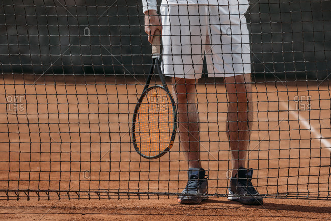 Cropped shot of tennis player with racket standing behind net