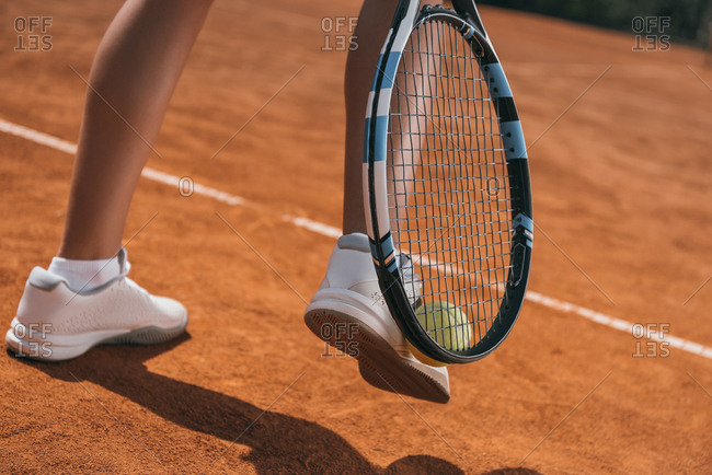Cropped shot of woman picking up tennis ball with racket and leg