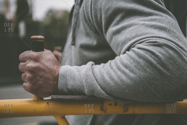 Cropped image of sportsman rocking press at horizontal bar