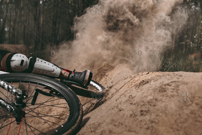 Cropped image of dust after racer riding bike
