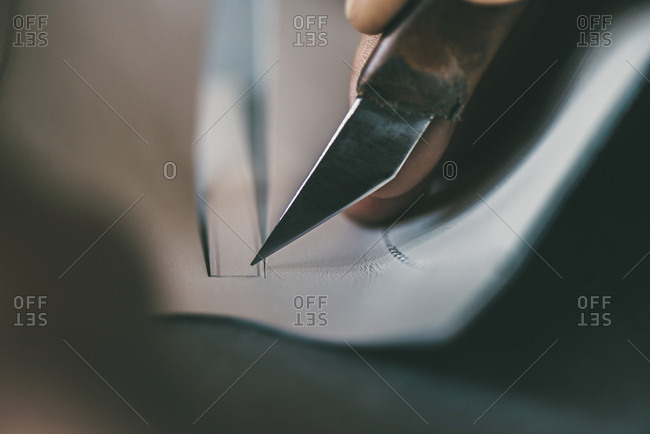 Close-up partial view of shoemaker cutting sole outline with knife