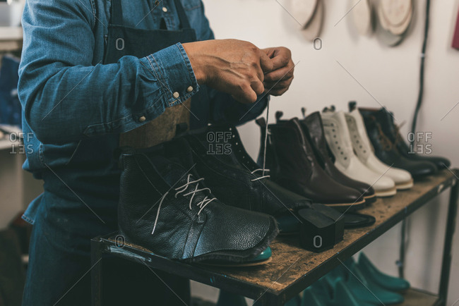 Cropped shot of shoemaker lacing up unfinished leather boots in workshop