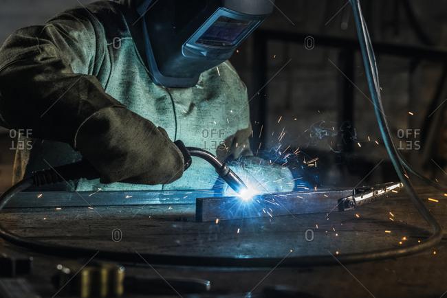 Manual worker in protective helmet with welding torch working in workshop