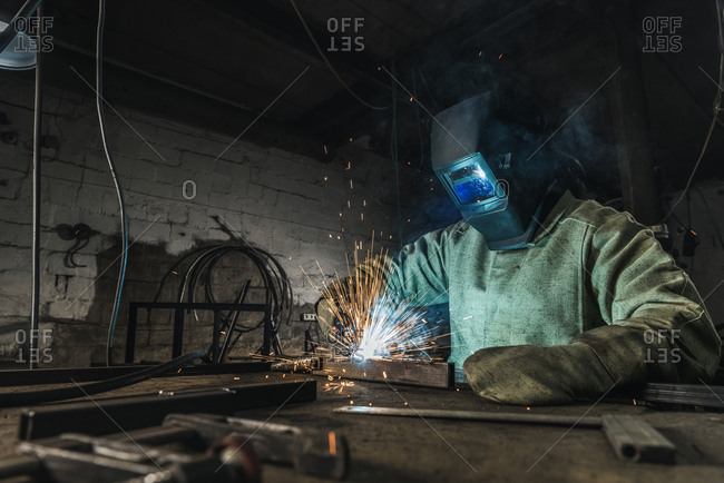 Manual worker in protective helmet with welding torch working in workshop