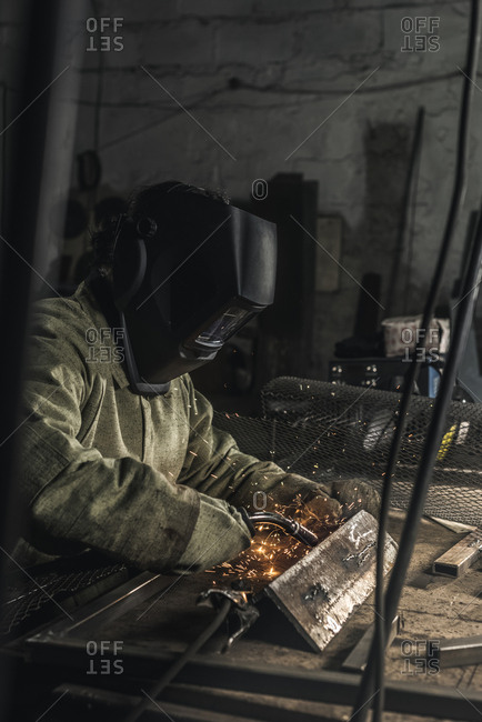 Side view of welder in protective work wear working with welding torch in workshop