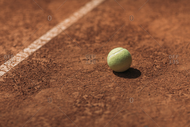 Tennis ball lying on court under bright sunlight