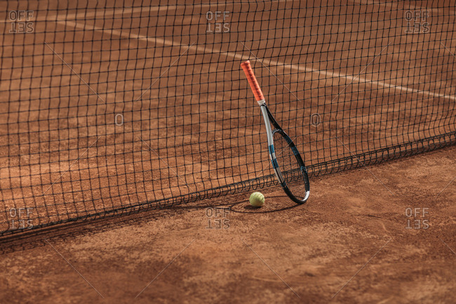Tennis ball and racket leaning on net