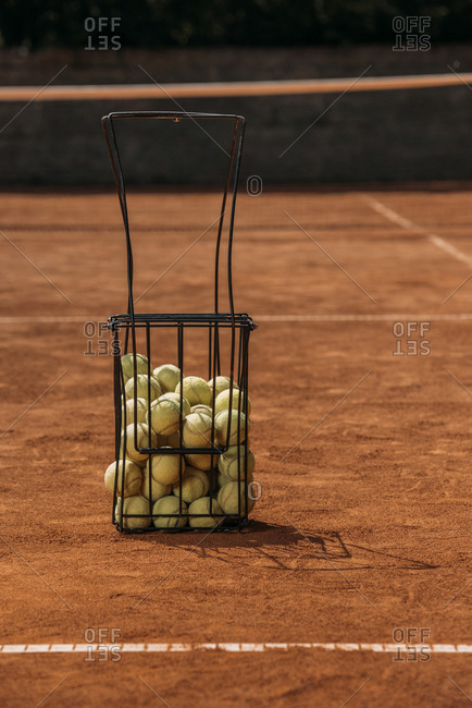 Basket of tennis balls standing on court