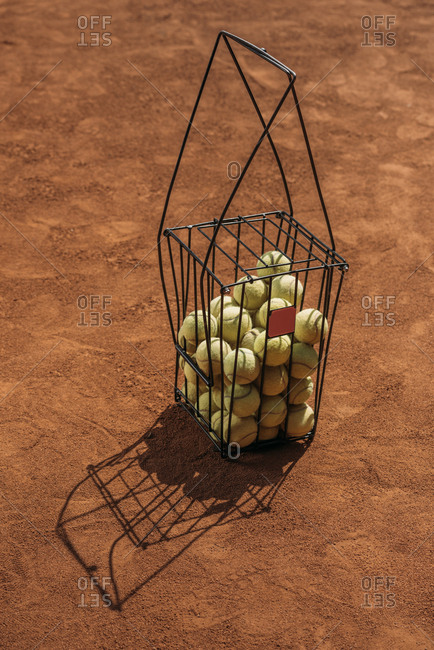 Basket of tennis balls standing on orange court surface