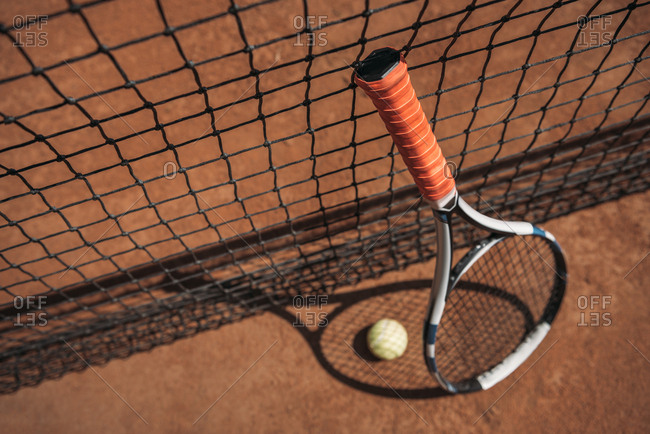 Close-up shot of tennis ball and racket leaning on net