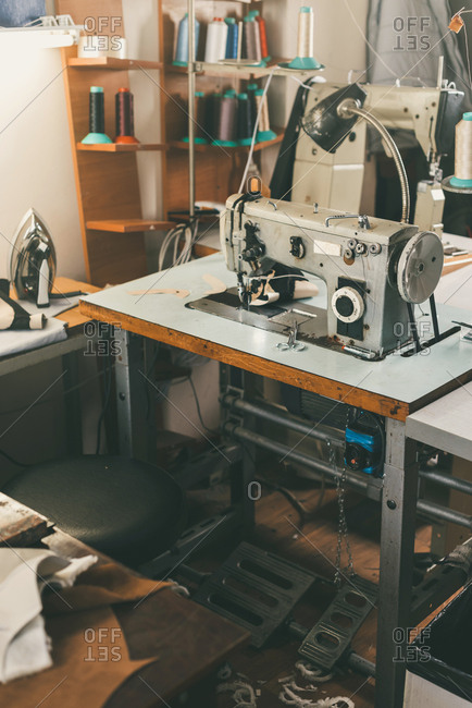 Workplace of seamstress at tailor shop with electrical industrial sewing machine