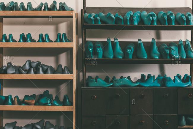 Plastic footwear work pieces on shelves at cobbler shop