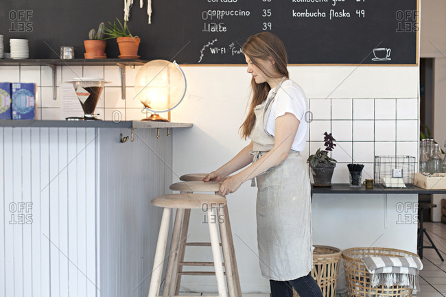 Young woman arranging stools in a cafe in Sweden