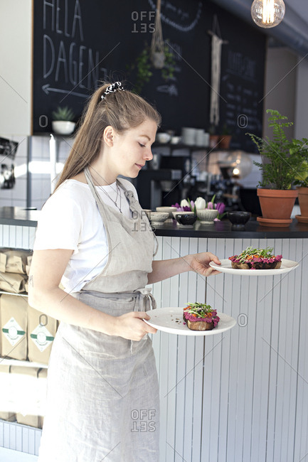 Young woman checking plates as she carries them to unseen customers in cafe in Sweden