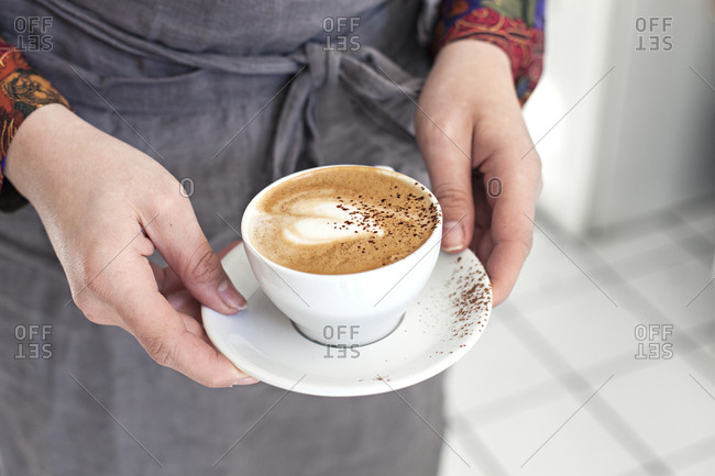Close up of woman's hands holding latte with heart shaped foam art