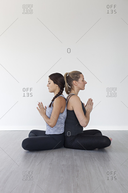 Women sitting cross legged back to back with hands in Anjali mudra doing yoga