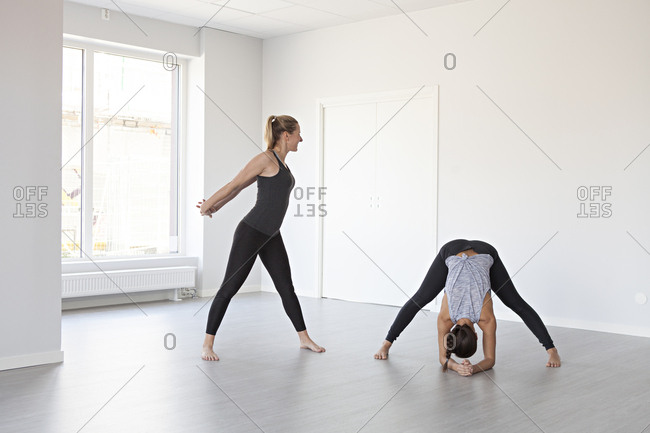 Young women in variation of triangle and wide legged forward bend poses during yoga class