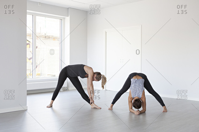 Yoga practitioners in triangle and wide legged forward bend poses