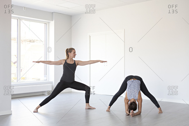 Young women in warrior two and wide legged forward bend poses during yoga session