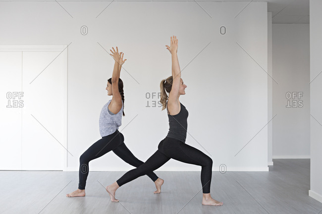 Young women in warrior one position during yoga session in studio