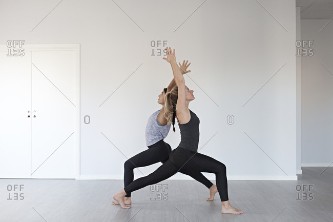 Young women in synchronized warrior one yoga positions in studio